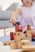 Caucasian girl playing with wooden blocks