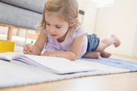 Caucasian girl doodling on floor