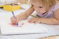 Caucasian girl drawing on floor