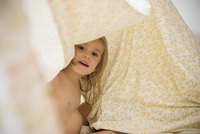 Caucasian girl playing under blankets
