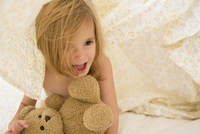 Caucasian girl playing with teddy bear under blankets