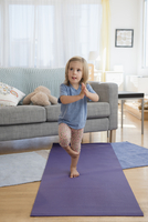 Caucasian girl practicing yoga in living room