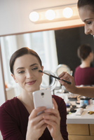 Woman having makeup applied by stylist