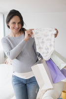 Pregnant Caucasian woman shopping for baby clothing