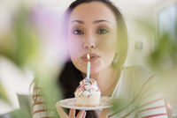 Woman blowing out birthday candle on cupcake 11018072985| 写真素材・ストックフォト・画像・イラスト素材|アマナイメージズ