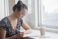Woman writing in coffee shop