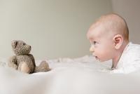Caucasian baby staring at teddy bear on bed 11018073017| 写真素材・ストックフォト・画像・イラスト素材|アマナイメージズ