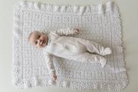Caucasian baby laying on blanket 11018073018| 写真素材・ストックフォト・画像・イラスト素材|アマナイメージズ