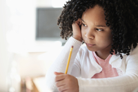 African American student writing in classroom