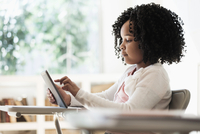 African American student using digital tablet in classroom