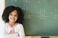 African American student smiling near chalkboard in classroom