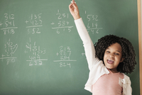 African American student cheering near chalkboard in classroom