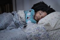 African American girl sleeping in bed 11018073045  写真素材・ストックフォト・画像・イラスト素材 アマナイメージズ