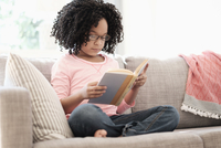 African American girl reading book on sofa