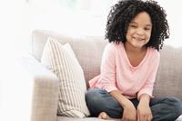 African American girl smiling on sofa 11018073051  写真素材・ストックフォト・画像・イラスト素材 アマナイメージズ