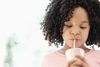African American girl drinking with straw