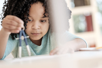 African American girl using compass in science classroom