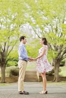 Pregnant Caucasian couple holding hands outdoors 11018073069| 写真素材・ストックフォト・画像・イラスト素材|アマナイメージズ