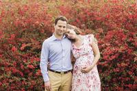 Pregnant Caucasian couple hugging outdoors 11018073074| 写真素材・ストックフォト・画像・イラスト素材|アマナイメージズ