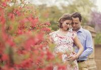 Pregnant Caucasian couple hugging outdoors
