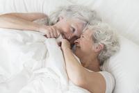 Older Caucasian lesbian couple laying in bed 11018073135| 写真素材・ストックフォト・画像・イラスト素材|アマナイメージズ
