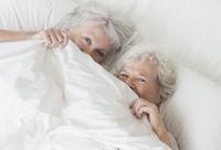 Older Caucasian lesbian couple laying in bed 11018073136| 写真素材・ストックフォト・画像・イラスト素材|アマナイメージズ