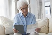 Older Caucasian woman using digital tablet to pay bills