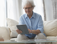 Older Caucasian woman using digital tablet on sofa