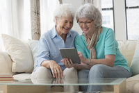 Older Caucasian woman lesbian couple using digital tablet