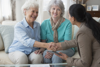 Woman shaking hands with older lesbian couple on sofa