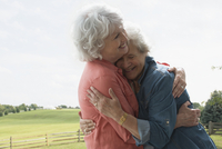 Older Caucasian lesbian couple hugging on farm