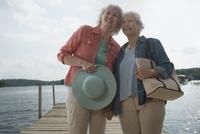 Older Caucasian lesbian couple walking on dock over lake 11018073145| 写真素材・ストックフォト・画像・イラスト素材|アマナイメージズ