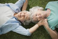 Older Caucasian lesbian couple laying in grass 11018073146| 写真素材・ストックフォト・画像・イラスト素材|アマナイメージズ
