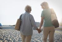 Older Caucasian lesbian couple walking on beach 11018073147| 写真素材・ストックフォト・画像・イラスト素材|アマナイメージズ