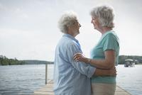 Older Caucasian lesbian couple hugging on dock over lake 11018073148| 写真素材・ストックフォト・画像・イラスト素材|アマナイメージズ