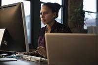 Hispanic businesswoman using computer in office