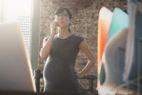 Pregnant Hispanic businesswoman talking on cell phone in office 11018073222| 写真素材・ストックフォト・画像・イラスト素材|アマナイメージズ