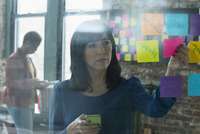 Hispanic businesswoman using adhesive notes in office