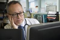 Asian doctor using computer in office 11018073254| 写真素材・ストックフォト・画像・イラスト素材|アマナイメージズ