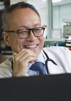 Asian doctor using computer in office 11018073256| 写真素材・ストックフォト・画像・イラスト素材|アマナイメージズ