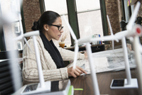 Hispanic businesswoman examining blueprints in office 11018073265| 写真素材・ストックフォト・画像・イラスト素材|アマナイメージズ