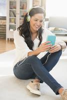 Hispanic woman listening to headphones in living room 11018073284| 写真素材・ストックフォト・画像・イラスト素材|アマナイメージズ