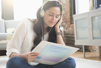 Hispanic woman listening to record in living room 11018073285| 写真素材・ストックフォト・画像・イラスト素材|アマナイメージズ