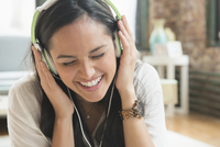 Hispanic woman listening to headphones in living room 11018073286| 写真素材・ストックフォト・画像・イラスト素材|アマナイメージズ