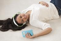 Hispanic woman listening to headphones on floor 11018073302| 写真素材・ストックフォト・画像・イラスト素材|アマナイメージズ