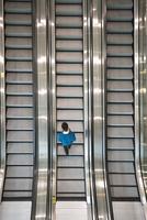 Mixed race businessman riding escalator