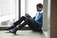 Mixed race businessman using digital tablet in office 11018073330  写真素材・ストックフォト・画像・イラスト素材 アマナイメージズ