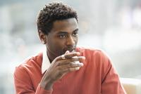 Mixed race businessman sitting in office 11018073341  写真素材・ストックフォト・画像・イラスト素材 アマナイメージズ
