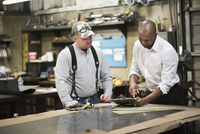 Worker and businessman using clipboard in workshop 11018073361| 写真素材・ストックフォト・画像・イラスト素材|アマナイメージズ