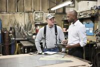Worker and businessman using digital tablet in workshop 11018073362| 写真素材・ストックフォト・画像・イラスト素材|アマナイメージズ
